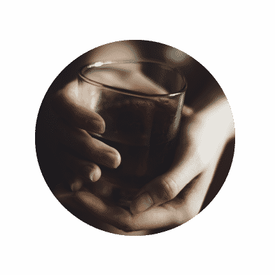Hands holding a glass of alcohol
